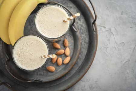 Banana smoothie with almond milk in glass on vintage round tray, top view Фото со стока