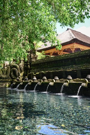 Holy spring water of sacred pool at Pura Tirta Empul Temple, Tampaksiring, Bali, Indonesia.