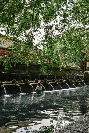 woman praying in holy spring water of sacred pool at Pura Tirta Empul Temple, Tampaksiring, Bali, Indonesia.
