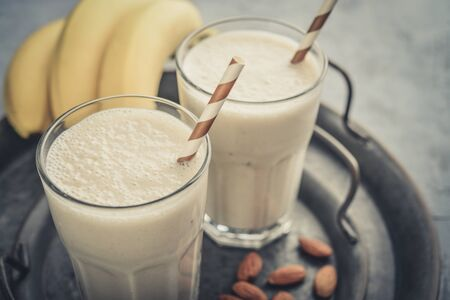 Banana smoothie with almond milk in glass on vintage round tray Фото со стока
