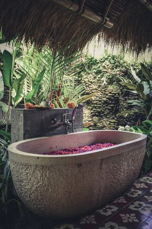 Bath tub with flower petals  - traditional part of  balinese spa treatment Фото со стока