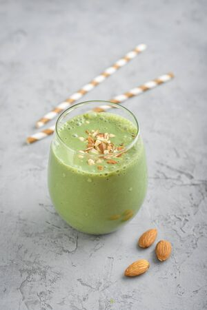Green smoothie with spinach and avocado in glass on grey background
