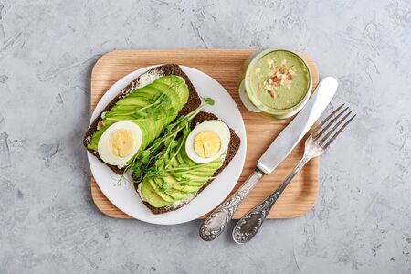 Avocado Sandwich with boiled Egg - sliced avocado and egg on rye toasted bread for healthy breakfast or snack on wooden tray, top view