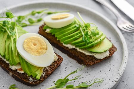 Avocado Sandwich with boiled Egg - sliced avocado and egg on rye toasted bread for healthy breakfast or snack