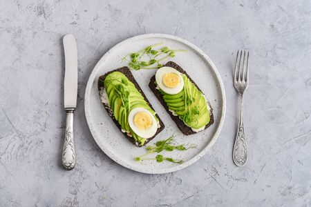 Avocado Sandwich with boiled Egg - sliced avocado and egg on rye toasted bread for healthy breakfast or snack, top view