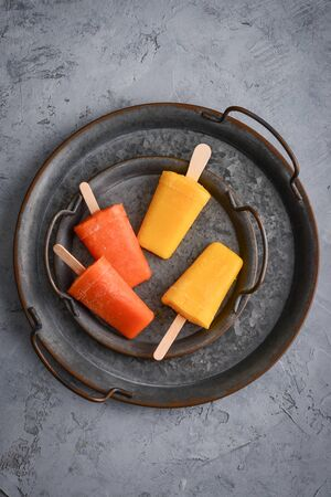 Papaya and mango ice cream stick on round metal tray on grey background, top view Фото со стока