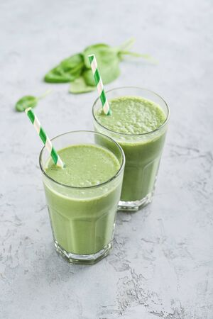 Green smoothie with spinach and avocado in glass on grey round tray