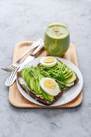 Avocado Sandwich with boiled Egg - sliced avocado and egg on rye toasted bread for healthy breakfast or snack on wooden tray