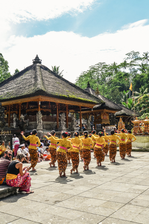 BALI, INDONESIA - MARCH 17, 2019: Balinese women in traditional costumes dance on territory of Holy Spring Water Temple (Pura Tirta Empul) on Bali, Indonesia. Редакционное