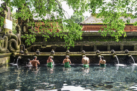 BALI, INDONESIA - MARCH 17, 2019: people praying in holy spring water of sacred pool at Pura Tirta Empul Temple, Tampaksiring, Bali, Indonesia.