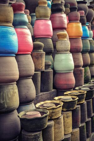 Local pottery craft shop on small street of Ubud, Bali. A lot of clay pots hang on strings as abstract background. 写真素材