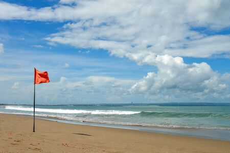 Petitenget Beach in Seminyak  with red flag at sunny day, popular Sunset Beach in Bali, Indonesia