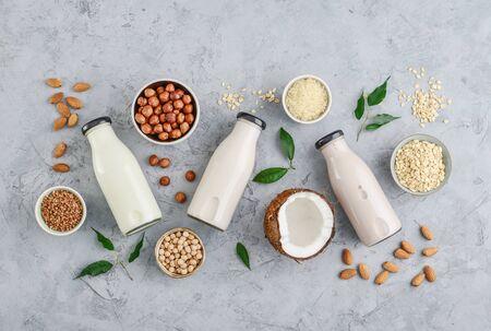 Assortiment ingrediënten voor biologische veganistische niet-zuivelmelk in kommen en flessen met veganistische melk op beton een keukentafel, bovenaanzicht Stockfoto