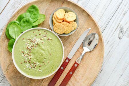 Grüne Brokkolisuppe mit Spinat auf weißem Holzhintergrund, Ansicht von oben