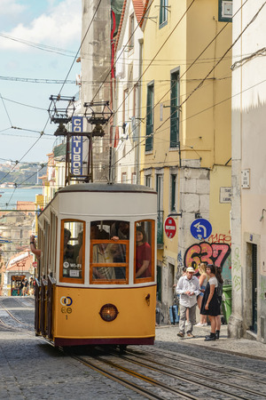LISBON, PORTUGAL - JULY 4, 2019: The Elevador or Ascensor da Bica is a popular tourist attraction in Chiado District, Lisbon. Tagus river on background.