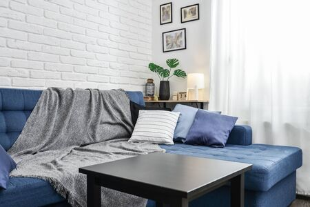 Bright living room in scandinavian style with blue couch, decorative pillows, white brick wall and white curtains. Design interior concept. Standard-Bild - 133224793