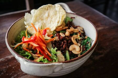 Organic Red Rice Nasi Goreng, vegetarian fried rice with loads of veggies, tofu & toasted cashews in bowl on wooden background Banco de Imagens