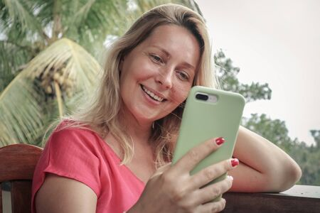 Adult blond woman using smart phone for video call outdoor on Bali island, Indonesia.