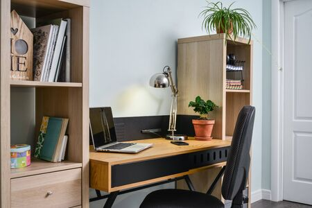 Light cozy teen room with white bookcases, working desk and laptop on it