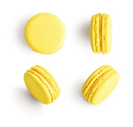 Set of yellow french macarons isolated on white background. Top view.