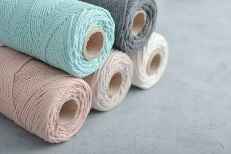 Macrame cotton cord spools in different pastel colors on grey concrete background, top view 版權商用圖片
