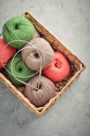 Colored yarn balls in rustic wicker basket on grey concrete background, top view