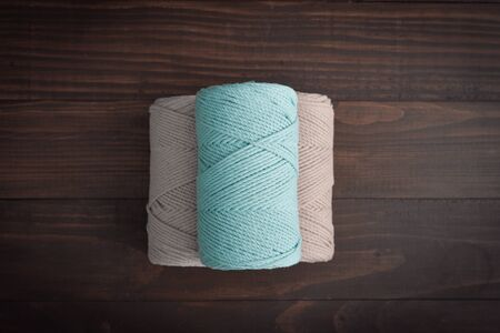 Macrame cotton cord spools in different pastel colors on wooden background