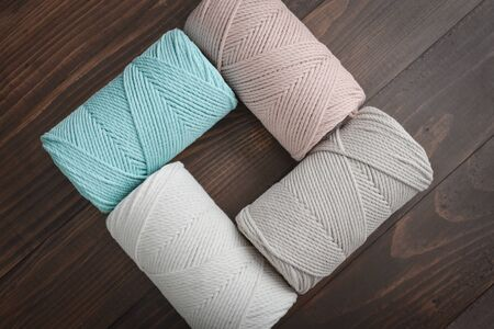 Macrame cotton cord spools in different pastel colors on wooden background, top view 版權商用圖片