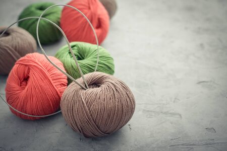 Colored yarn balls on grey concrete background closeup