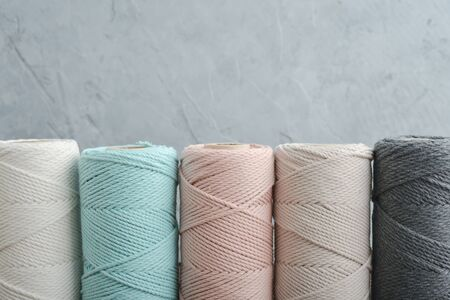 Macrame cotton cord spools in different pastel colors on grey concrete background 版權商用圖片