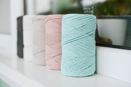 Macrame cotton cord spools in different pastel colors on windowsill at home