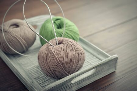 Colored yarn balls on wooden background closeup
