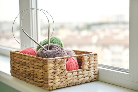 Colored yarn balls in wicker  basket on windowsill at home closeup