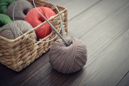Colored yarn balls in rustic wicker basket on blue couch closeup
