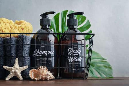 Plastic brown bottles with dispenser pumps  in  metal basket, towels  and sponge on grey background.