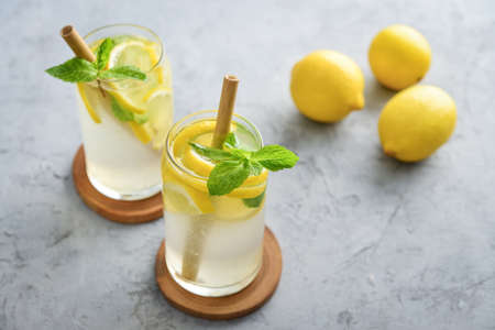 Lemonade with lemon and basil, cold refreshing drink in glasses on grey background Foto de archivo - 153506862