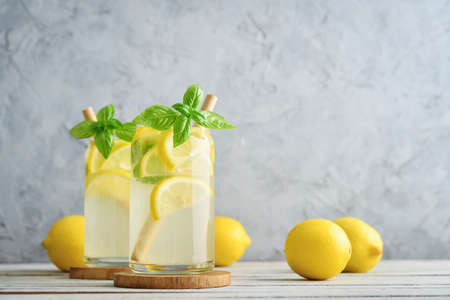 Lemonade with lemon and basil, cold refreshing drink in glasses on grey background Foto de archivo