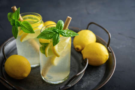 Lemonade with lemon and basil, cold refreshing drink in glasses on black background Foto de archivo - 153506946