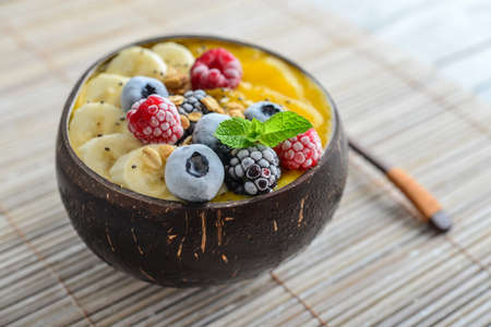 Mango smoothie bowl with banana, blueberry, blackberry, raspberry, granola and chia seeds in bowl from coconut shell, closeup Foto de archivo