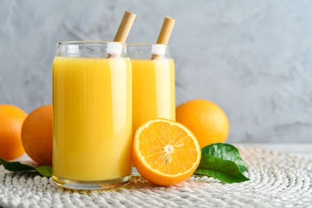 Two Glasses of Fresh Orange Juice with bamboo drinking straws on light wooden background Foto de archivo - 153506657