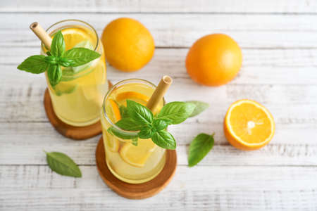 Lemonade with orange and basil, cold refreshing drink in glasses on grey background Foto de archivo