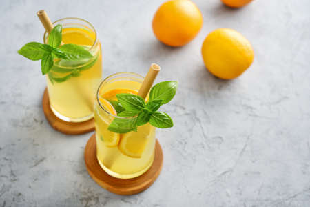 Lemonade with orange and basil, cold refreshing drink in glasses on grey background Foto de archivo - 153506968