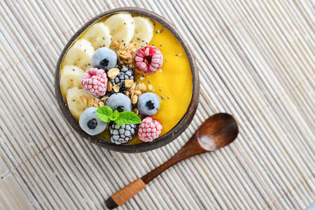 Mango smoothie bowl with banana, blueberry, blackberry, raspberry, granola and chia seeds in bowl from coconut shell, top view Foto de archivo