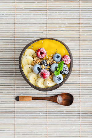 Mango smoothie bowl with banana, blueberry, blackberry, raspberry, granola and chia seeds in bowl from coconut shell, top view Foto de archivo - 153689615