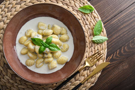Homemade gnocchi with creamy gorgonzola sauce in brown plate on wooden background, top view Foto de archivo