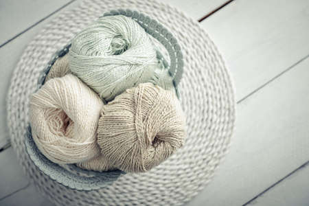 Colored yarn balls and knitting needles in basket on light background, top view Foto de archivo - 153506900