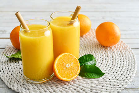 Two Glasses of Fresh Orange Juice with bamboo drinking straws on light wooden background