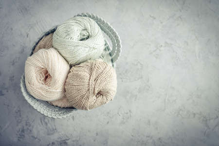 Colored yarn balls and knitting needles in basket on light background, top view Foto de archivo
