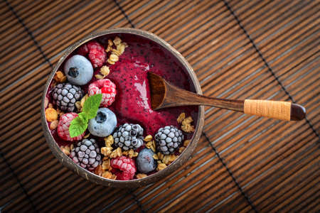 Acai smoothie bowl with blueberry, blackberry, raspberry, granola and chia seeds in bowl from coconut shell, top view Foto de archivo - 153689465
