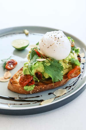 Avocado toast with poached egg, salad leves and cherry tomato for breackfast closeup Foto de archivo - 154473966